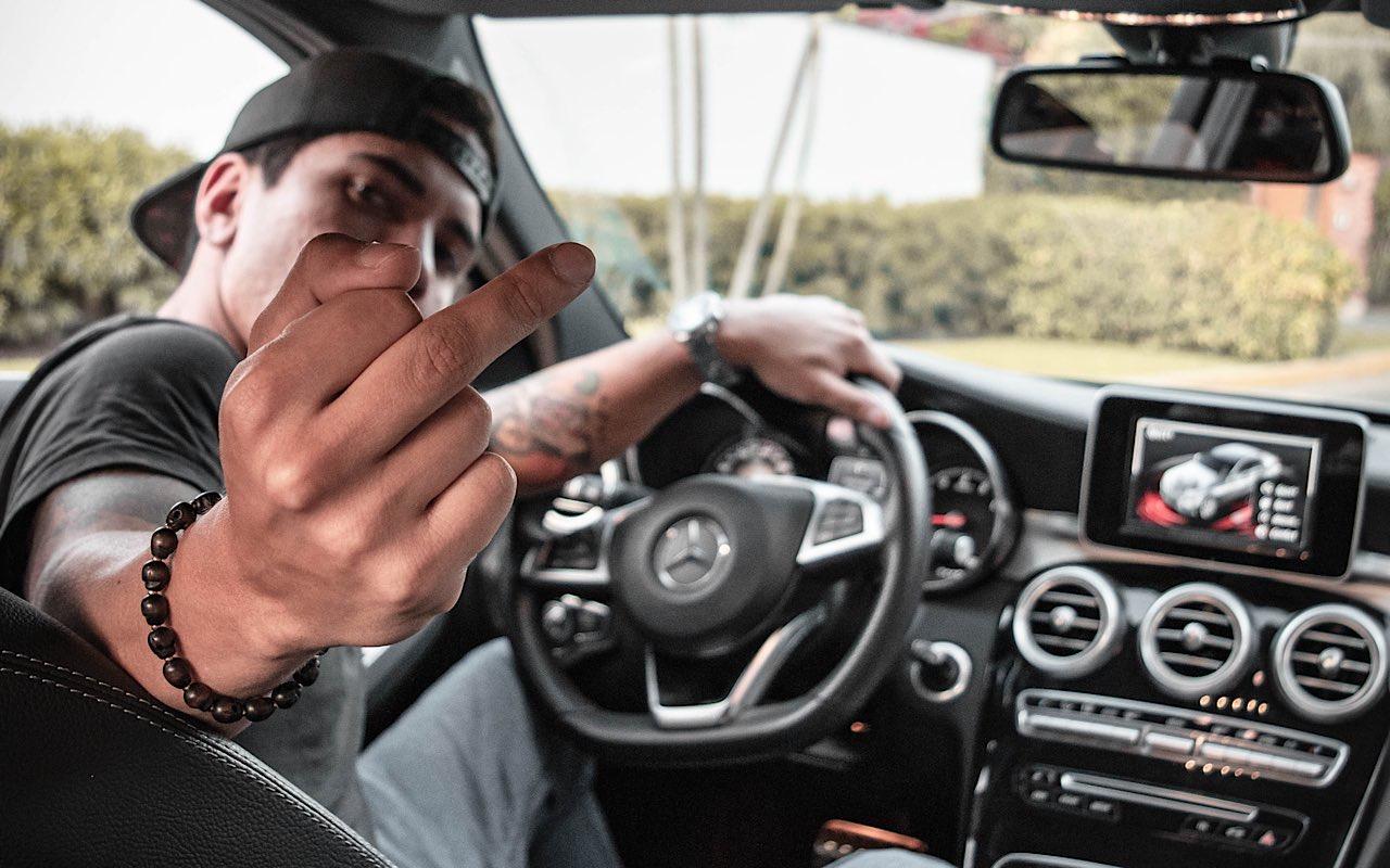 Man in auto Met middelvinger
